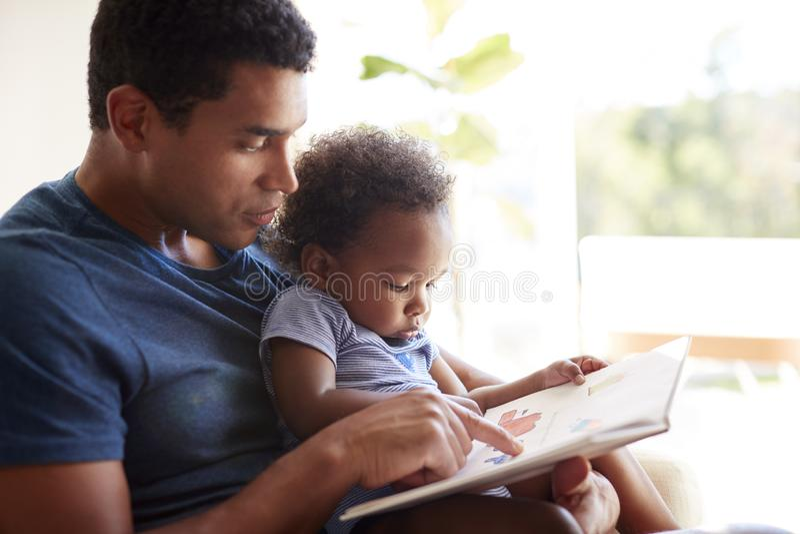Stäng sig upp av den unga vuxna afrikansk amerikanfadern som läser en bok med hans två den åriga sonen, slut upp, sidosikten som  arkivfoton