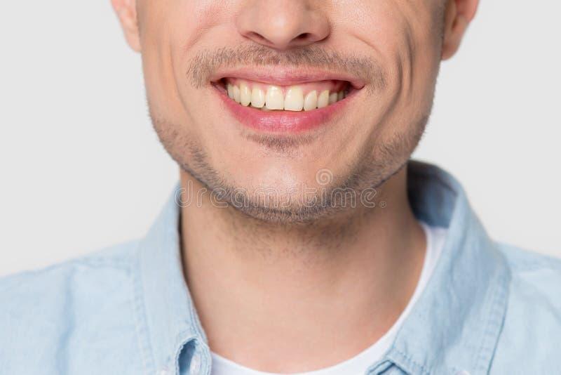 Stäng sig upp av det europeiska manliga leendet som isoleras på grå bakgrund royaltyfri fotografi