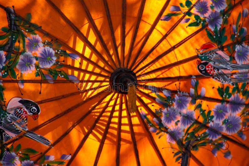 Stäng sig upp av det färgrika orange pappers- paraplyet som målas med blommor och exponeras av solljus - Chiang Mai, Thailand royaltyfria bilder