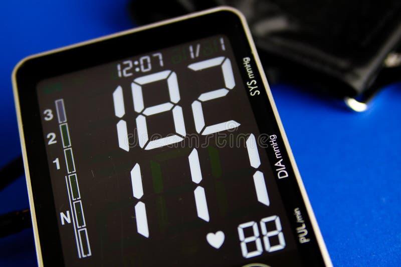 Stäng sig upp av digital sphygmomanometerbildskärm med manschetten som visar högt diastolic och systolic blodtryck arkivbilder