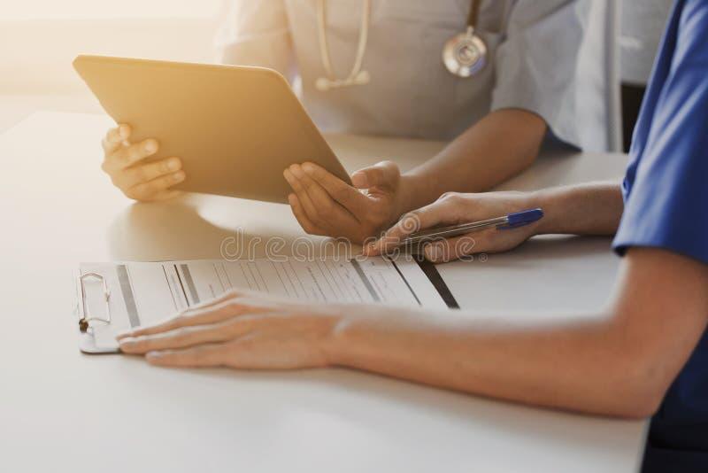 Stäng sig upp av doktorer med minnestavlaPC på sjukhuset royaltyfri foto