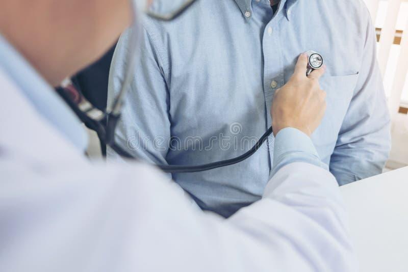 Stäng sig upp av doktorn som lyssnar till det tålmodiga hjärtslaget med stethosco royaltyfri bild