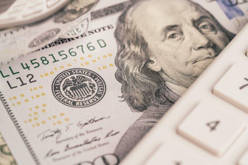 Stäng sig upp av dollarsedeln för USA Amerika med FED, emblem för federal reserv, och Franklin vänder mot med räknemaskinen genom royaltyfria bilder