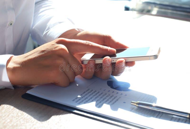 Stäng sig upp av en affärskvinna som använder mobilen royaltyfri fotografi