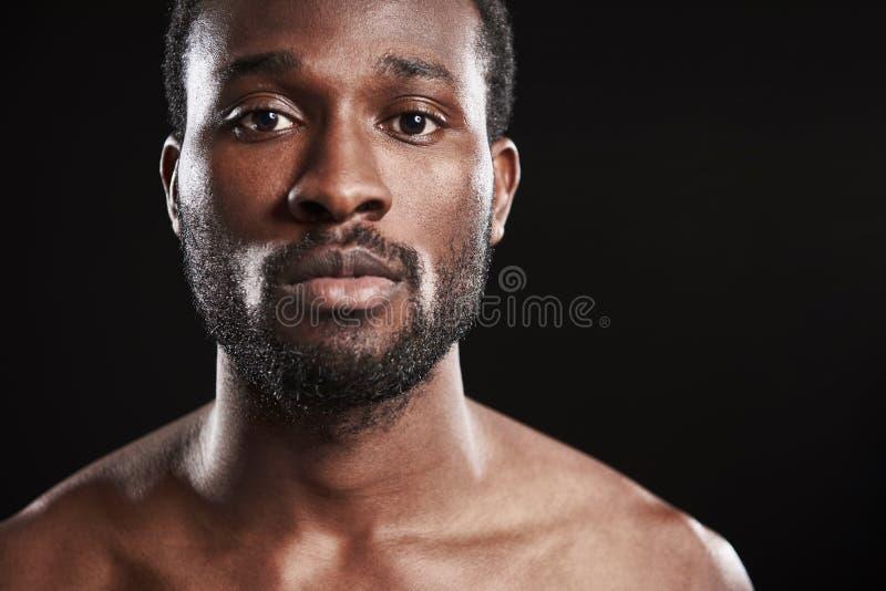 Stäng sig upp av en afro amerikansk man som ser kameran royaltyfri foto