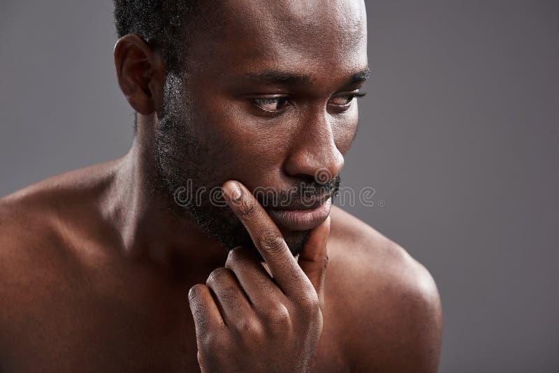 Stäng sig upp av en allvarlig afro amerikansk man som funderar på hans liv arkivfoto