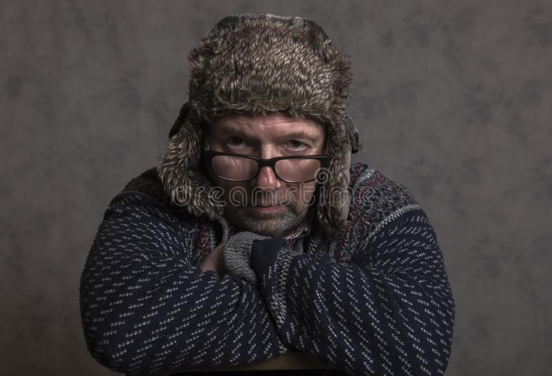 Stäng sig upp av en allvarlig mogen man som bär en vinterhatt arkivfoton