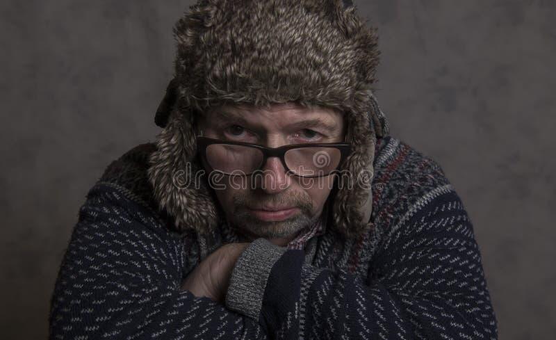 Stäng sig upp av en allvarlig mogen man som bär en vinterhatt arkivbild