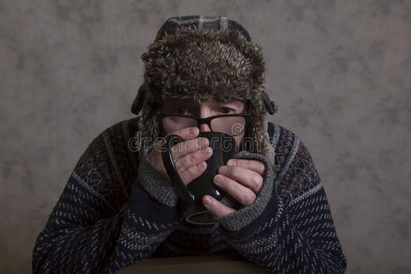 Stäng sig upp av en allvarlig mogen man som bär en vinterhatt och dricker en varm drink royaltyfri bild