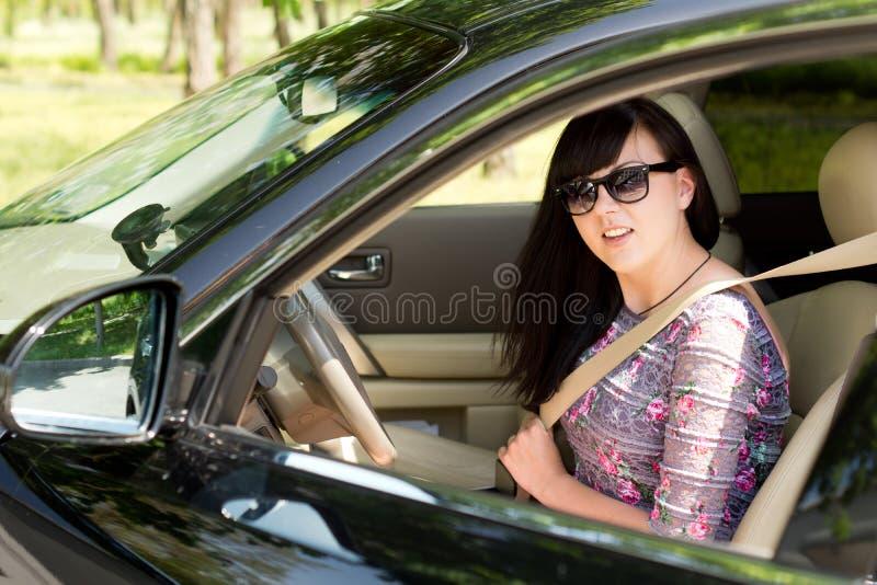 Stäng sig upp av en attraktiv brunettkvinna i en bil fotografering för bildbyråer