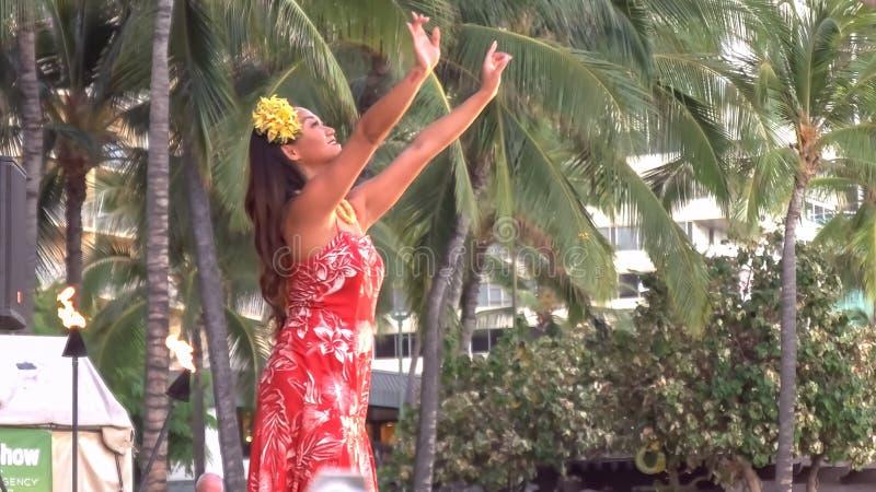 Stäng sig upp av en attraktiv kvinnlig hawaiansk huladansare i rött utföra för klänning arkivfoto