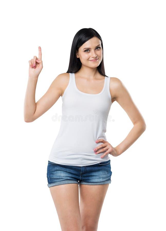 Stäng sig upp av en brunettdam i en ärmlös tröja och grov bomullstvill som pekar upp hennes finger Ett begrepp av en ny idé arkivfoton