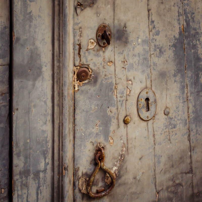 Stäng sig upp av en dörr med tre forntida lås och en gammal knackare arkivbilder