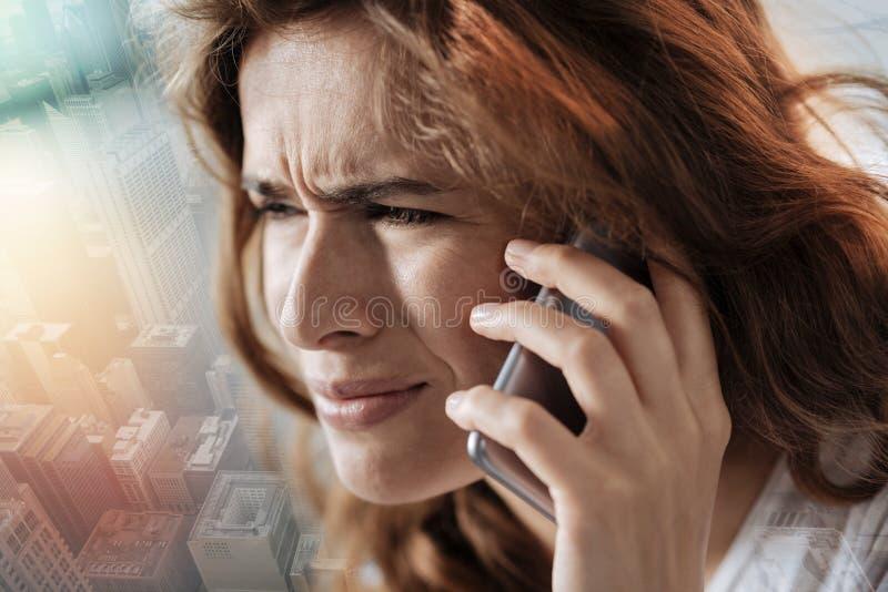 Stäng sig upp av en deprimerad kvinna som talar på telefonen royaltyfri fotografi
