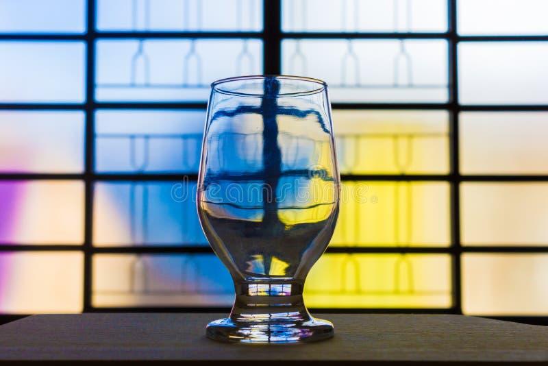 Stäng sig upp av en exponeringsglaskopp på en trätabell royaltyfri foto