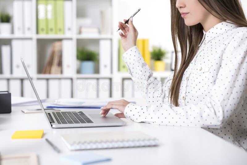 Stäng sig upp av en flicka i en prickskjorta på hennes bärbar dator i regeringsställning arkivfoton