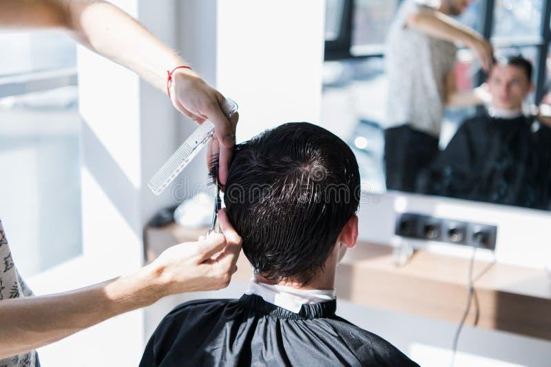 Stäng sig upp av en frisyr på hårsalongen Barberare som triming en klients hår med sax arkivbild