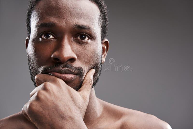 Stäng sig upp av en fundersam afro amerikansk man som funderar på hans problem arkivfoton