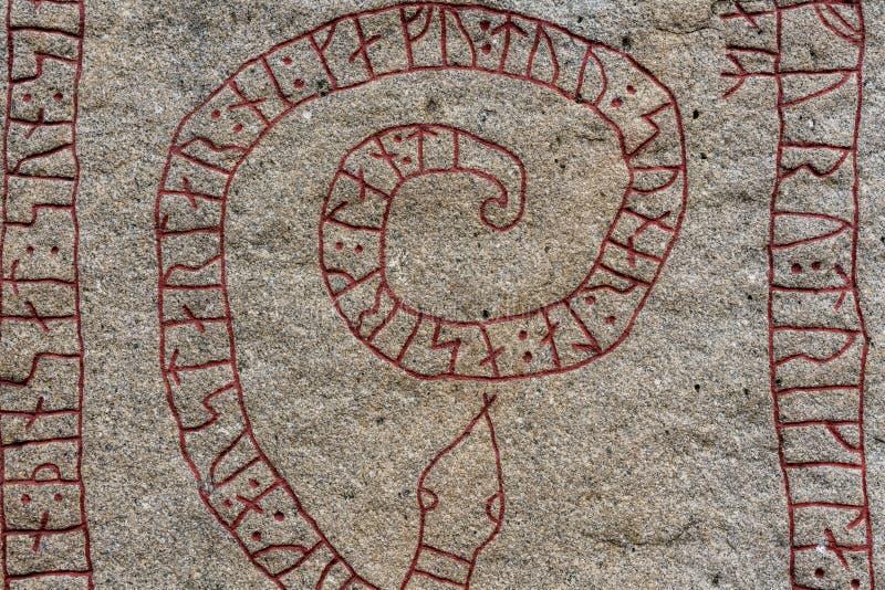 Stäng sig upp av en gammal runsten med röda runor i formen av ett s royaltyfri bild