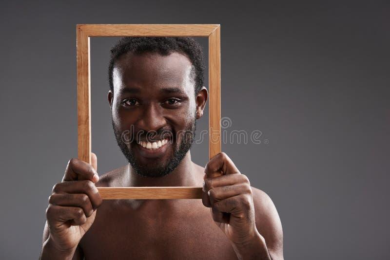 Stäng sig upp av en glad stilig man som rymmer en fotoram royaltyfri bild