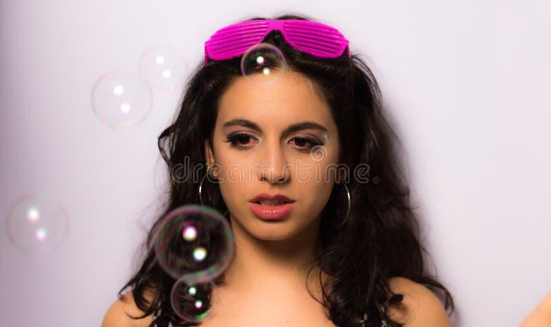 Stäng sig upp av en härlig flicka med yrkesmässigt smink som blåser såpbubblor runt om henne royaltyfri fotografi