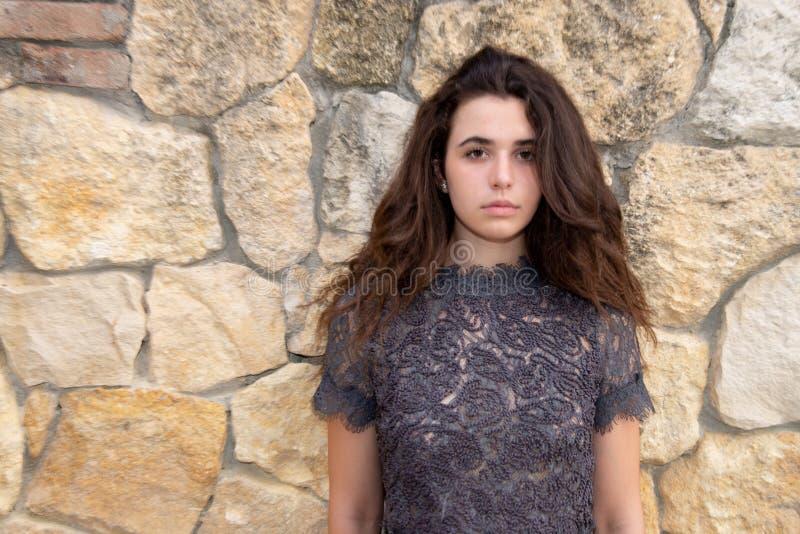 Stäng sig upp av en härlig ung sinnlig flicka, med en svart snör åt klänningslivet som ser kameran royaltyfria bilder