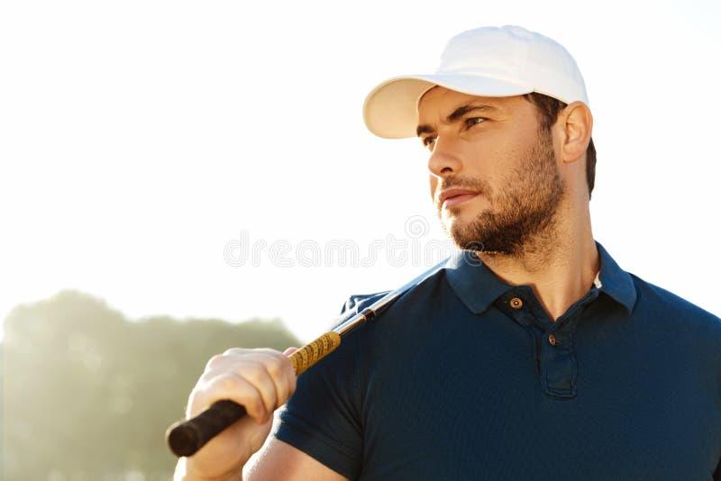 Stäng sig upp av en hållande golfklubb för stilig manlig golfare fotografering för bildbyråer