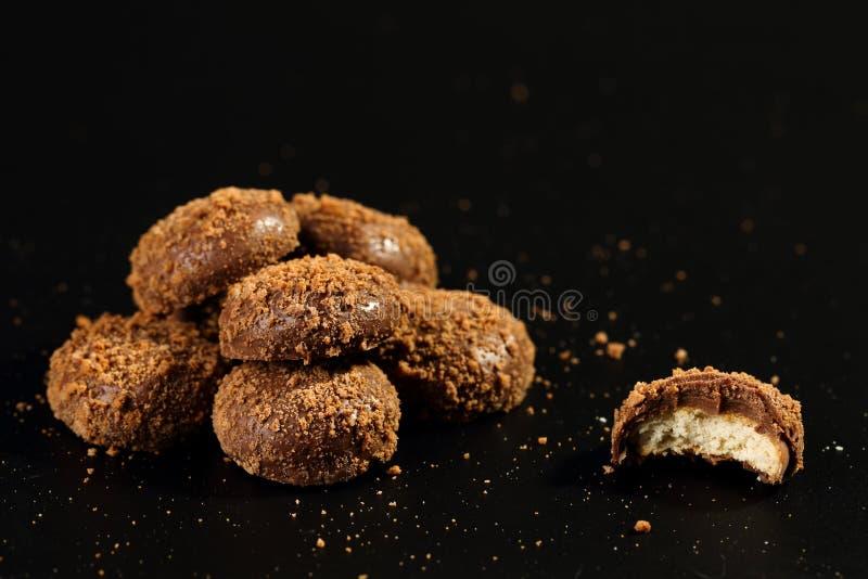 Stäng sig upp av en hög, och halvan bet läckra frasiga karamellkex som täckas med, mjölkar choklad- och kexpartiklar royaltyfri bild