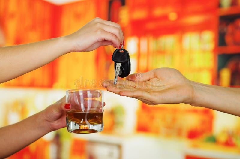 Stäng sig upp av en hand som rymmer ett exponeringsglas av whisky och ger hennes tangenter till en annan person, i stångbakgrund arkivfoton