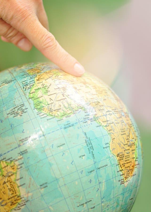 Stäng sig upp av en jordklotvärldskarta med ett pekfinger på det royaltyfri fotografi