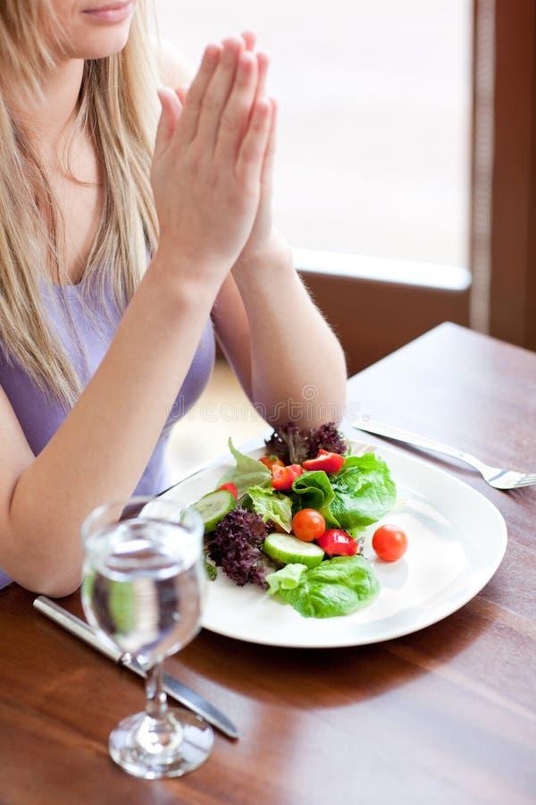 Stäng sig upp av en kvinna som ber, innan du äter royaltyfria bilder