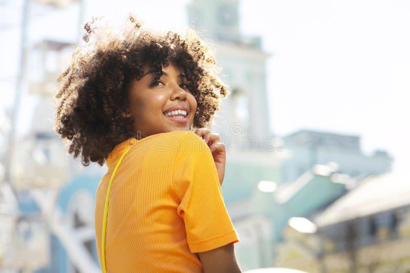 Stäng sig upp av en lycklig lockig-haired flicka som ler under sight arkivfoton