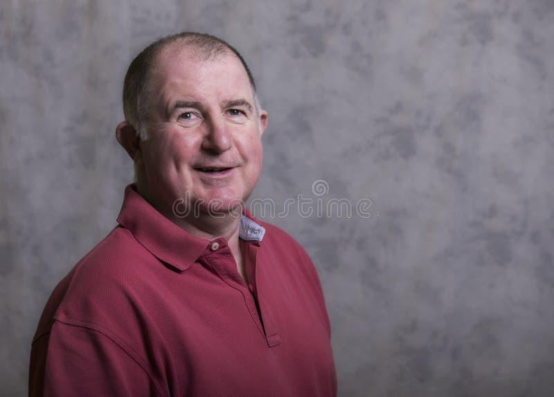 Stäng sig upp av en lycklig mogen man på en grå bakgrund royaltyfri fotografi