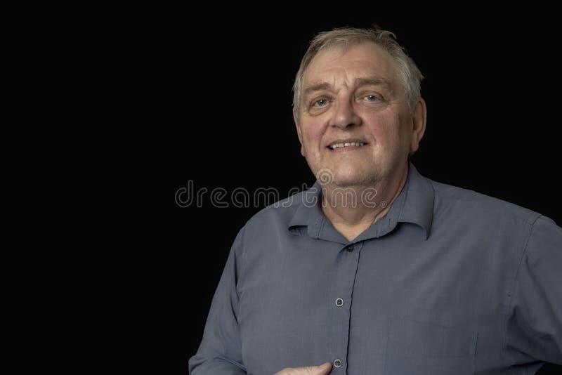 Stäng sig upp av en lycklig mogen man på en svart bakgrund royaltyfria foton