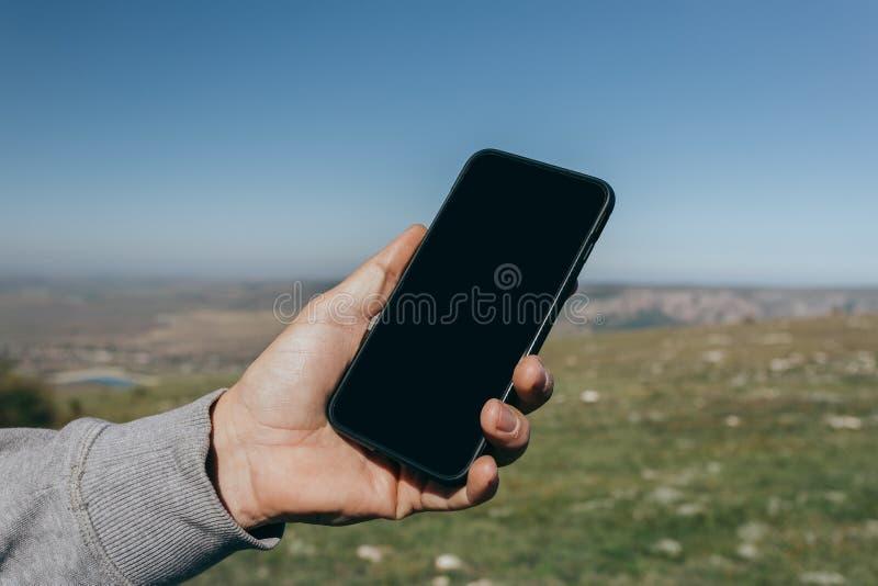 Stäng sig upp av en man som använder den utomhus- telefonen royaltyfri fotografi
