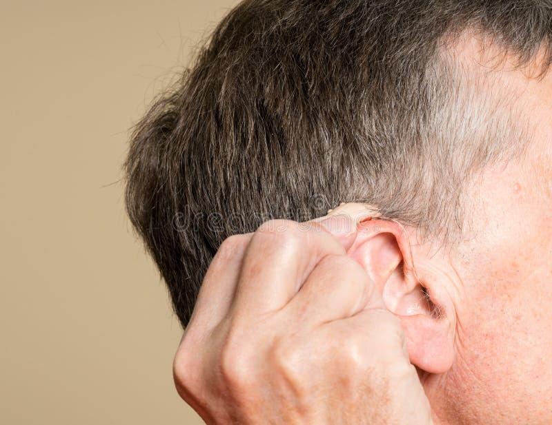 Stäng sig upp av en mycket liten modern hörapparat bak örat royaltyfria foton
