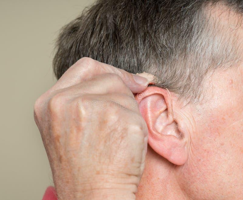 Stäng sig upp av en mycket liten modern hörapparat bak örat royaltyfri foto