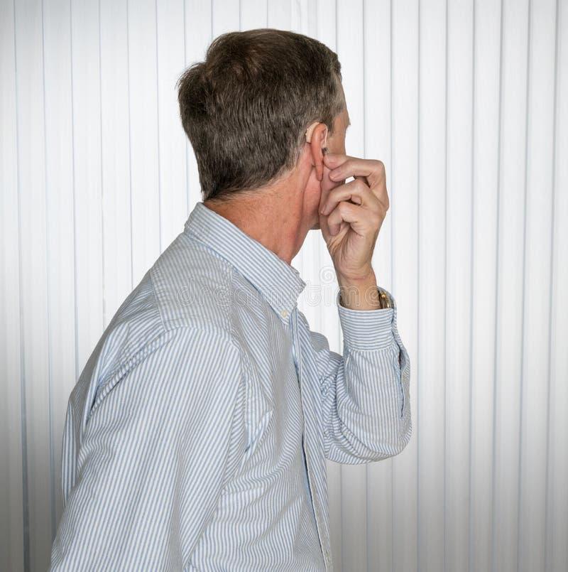 Stäng sig upp av en mycket liten modern hörapparat med den höga mannen arkivfoton