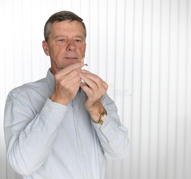 Stäng sig upp av en mycket liten modern hörapparat med den höga mannen royaltyfria foton