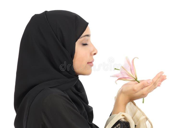 Stäng sig upp av en profil av en arabisk kvinna som luktar en blomma royaltyfri foto
