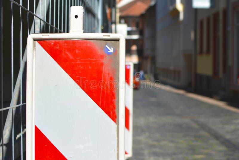 Stäng sig upp av en röd och vit randig säkerhetsfyr framme av barriären för konstruktionsplatsen med gatan i bakgrund royaltyfri foto