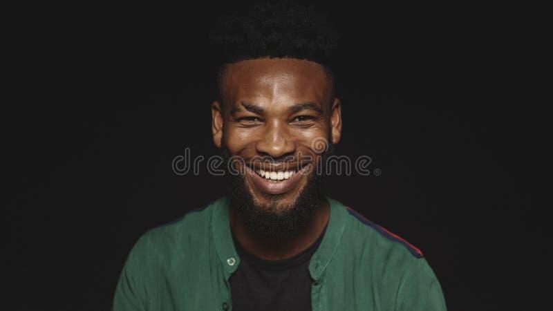 St?ng sig upp av en skratta afrikansk man royaltyfri bild