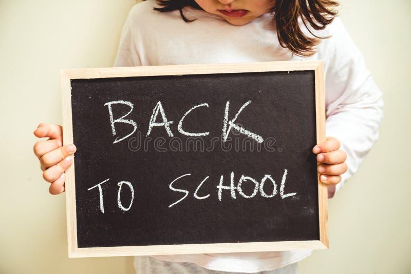 Stäng sig upp av en svart svart tavla med orden tillbaka till skolan som är skriftlig på den som rymms av ett barn som trutar arkivbild