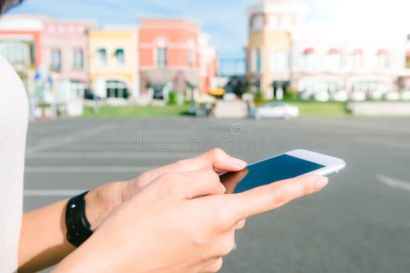 Stäng sig upp av en ung asiatisk kvinna som använder smartphonen i stad och trevlig blå himmel royaltyfri foto