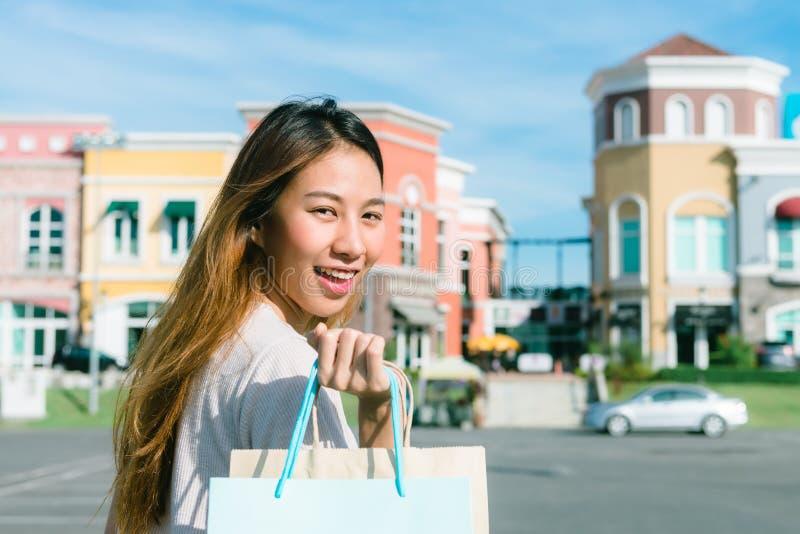 Stäng sig upp av en ung asiatisk kvinna som shoppar en utomhus- loppmarknad med en bakgrund av pastellfärgade bulidings och blå h royaltyfri fotografi