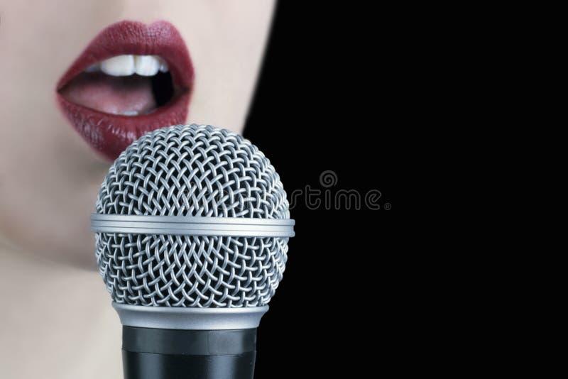Stäng sig upp av en ung kvinna med röda kanter som sjunger till microphonen arkivfoton