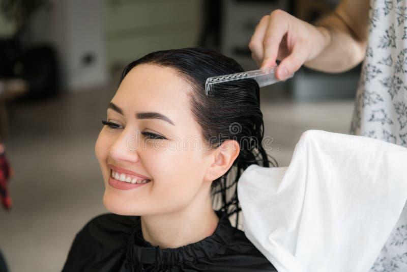 Stäng sig upp av en ung lycklig härlig kvinna som ler till kameran medan den yrkesmässiga frisören som in slår in hennes våta hår royaltyfria bilder