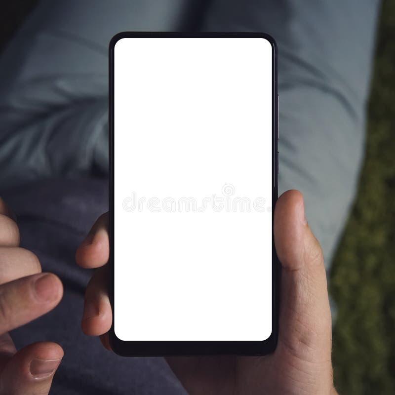 Stäng sig upp av en ung man som sitter den långa hållande smartphonen med den vita skärmen Personen är on-line från en smartphone arkivbild