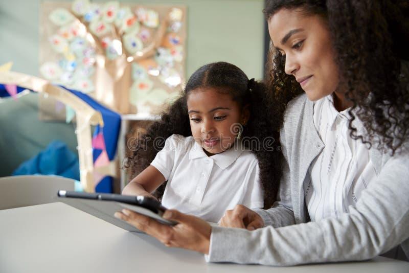 Stäng sig upp av en ung svart skolflicka som sitter på en tabell i ett klassrum för begynnande skola som lär en på en med en lära arkivfoton