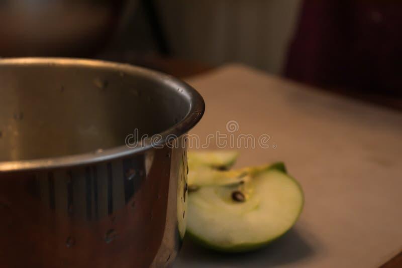 Stäng sig upp av en våt metallbunke med ett skivat äpple i bakgrunden arkivbilder